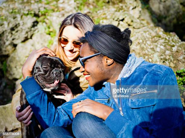 Mixed race female friends with French Bulldog in park