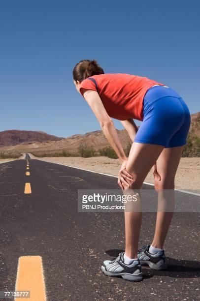 mixed race female runner on road - bemühung stock-fotos und bilder