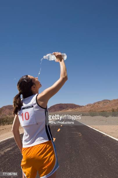mixed race female runner pouring water on face - forward athlete stock pictures, royalty-free photos & images