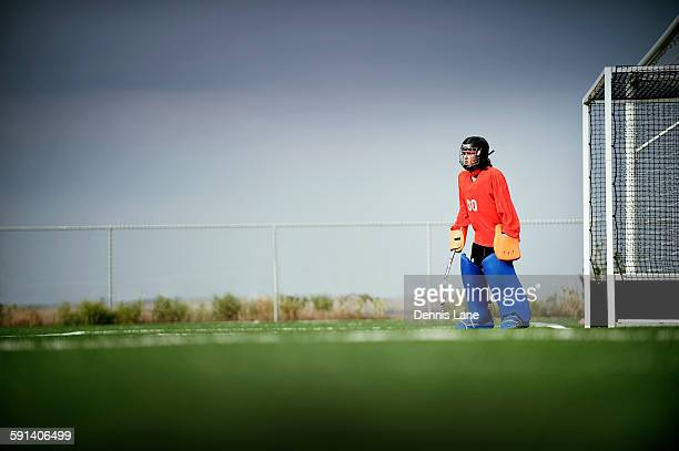 mixed race field hockey goalie standing by goal - field hockey stock pictures, royalty-free photos & images