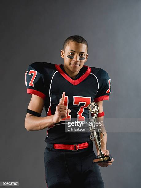 mixed race football player holding trophy and gesturing - eye black stock photos and pictures