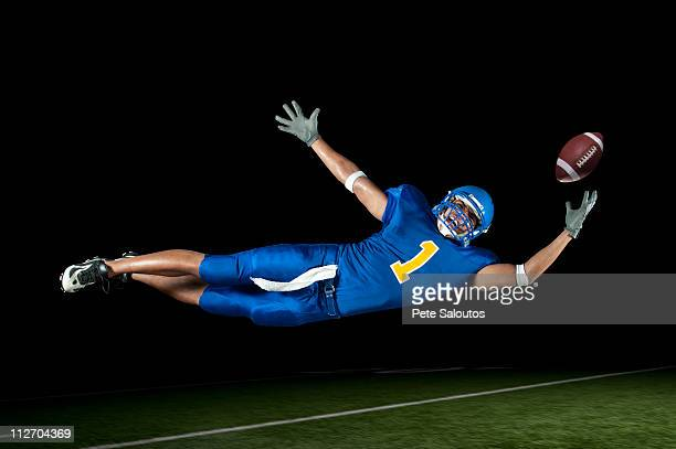 mixed race football player jumping in mid-air catching football - wide receiver athlete stock pictures, royalty-free photos & images