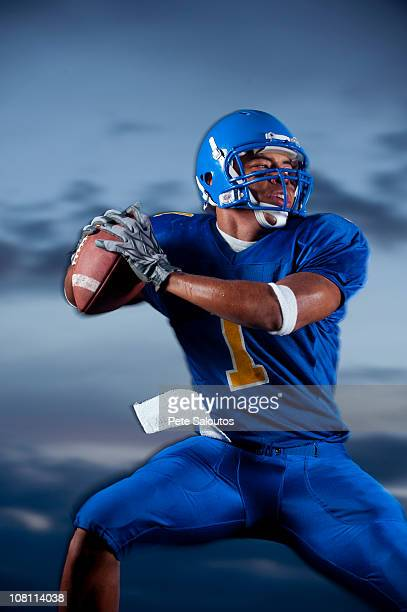 mixed race football player preparing to throw football - quarterback stock photos and pictures