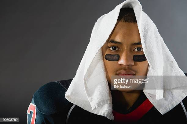 mixed race football player with towel on head - eye black stock photos and pictures