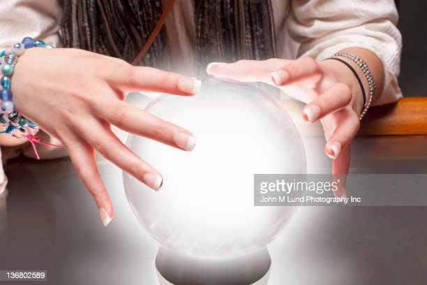 mixed race fortune teller with crystal ball - fate stock photos and pictures