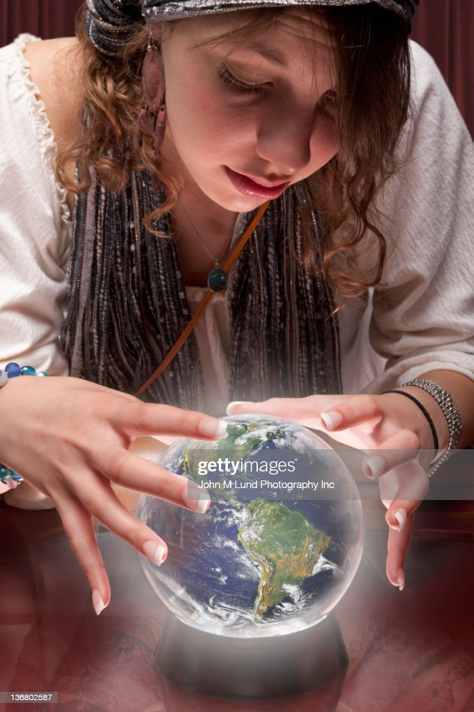 Mixed race fortune teller with crystal ball shaped like globe : Stock Photo
