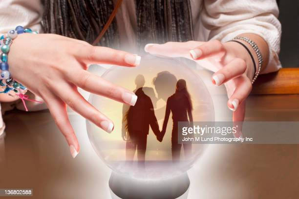 Mixed race fortune teller with crystal ball with people inside