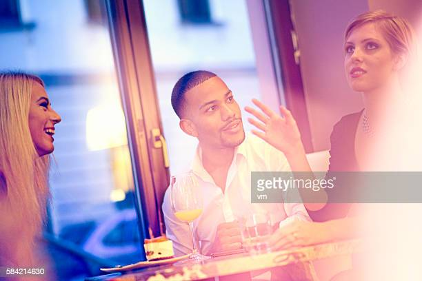 Mixed race frends sitting in bar