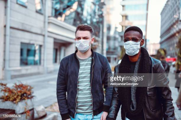 mixed race gay couple on their way to anti pollution protest - protestor mask stock pictures, royalty-free photos & images