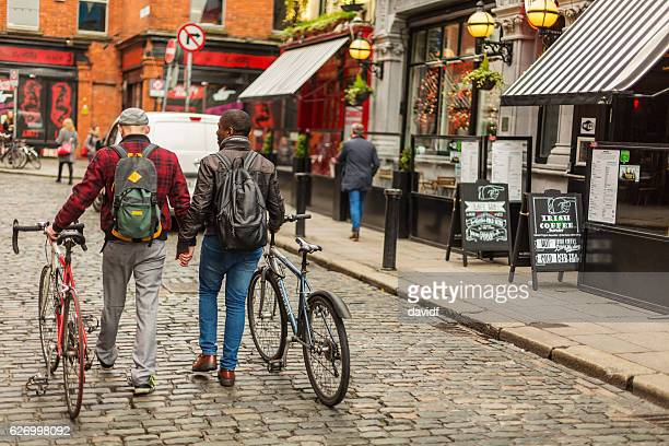 mixed race gay couple with bicycles in the city - dublin stock pictures, royalty-free photos & images