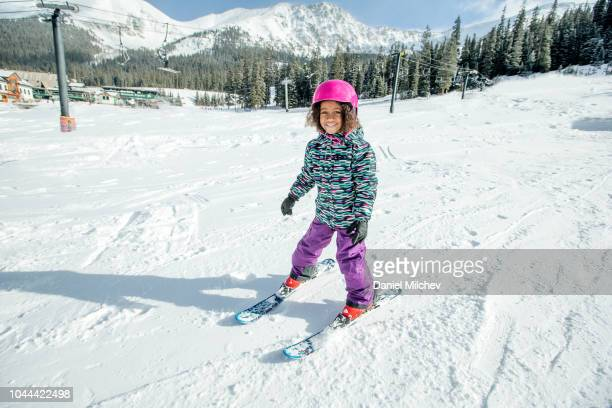 Mixed race gir smiling at the camera while skiing on a sunny day in the Colorado mountains.