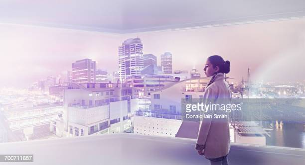 Mixed Race girl admiring cityscape from window