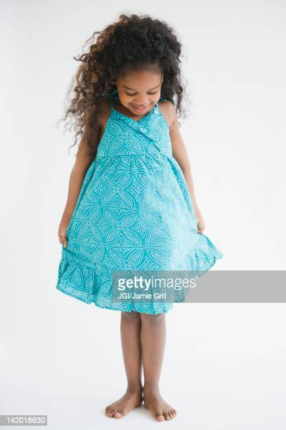 mixed race girl admiring her dress - cut out dress stock pictures, royalty-free photos & images