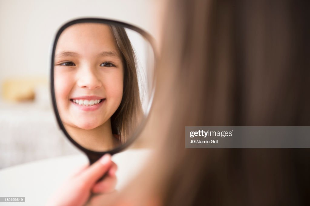 Mixed race girl admiring herself in mirror : Stock Photo