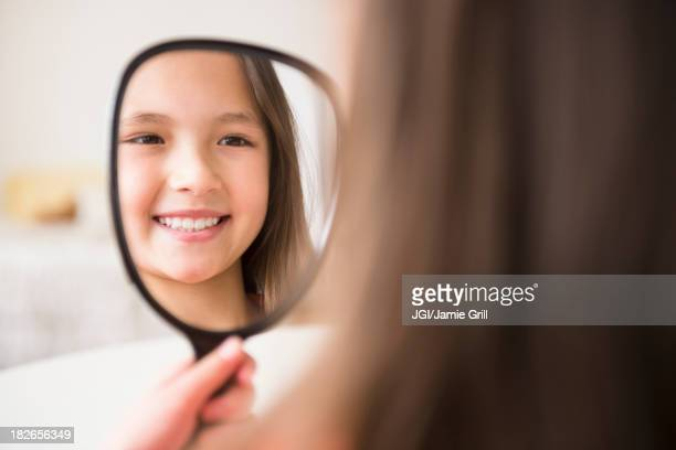 Mixed race girl admiring herself in mirror