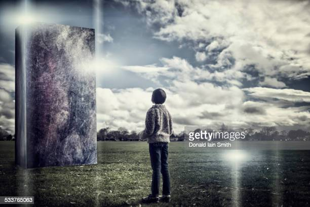 Mixed race girl admiring stone sculpture in field