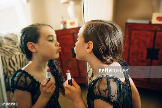 mixed race girl applying lipstick in mirror - kids makeup stock pictures, royalty-free photos & images