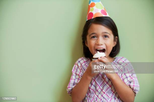 Mixed race girl at party eating cupcake