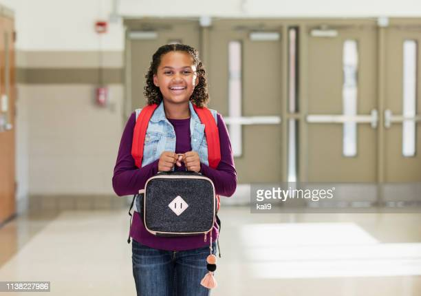 mixed race girl at school carrying lunch box - lunch box stock pictures, royalty-free photos & images