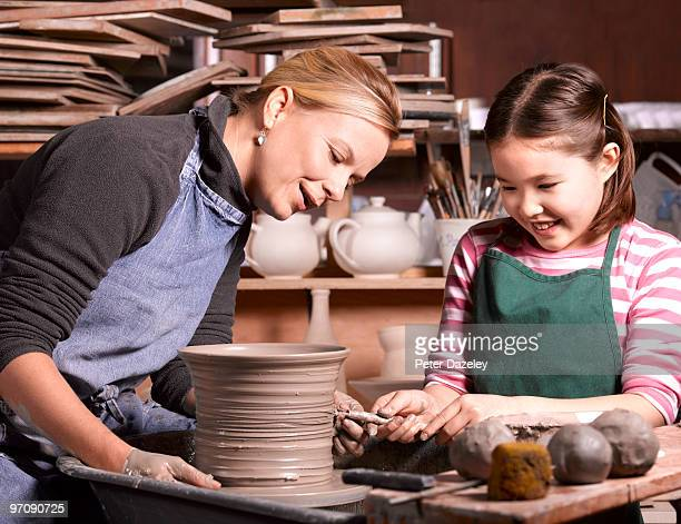 mixed race girl being taught pottery by teacher