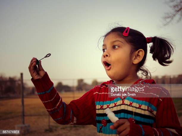 mixed race girl blowing bubbles in field - punjab pakistan stock photos and pictures