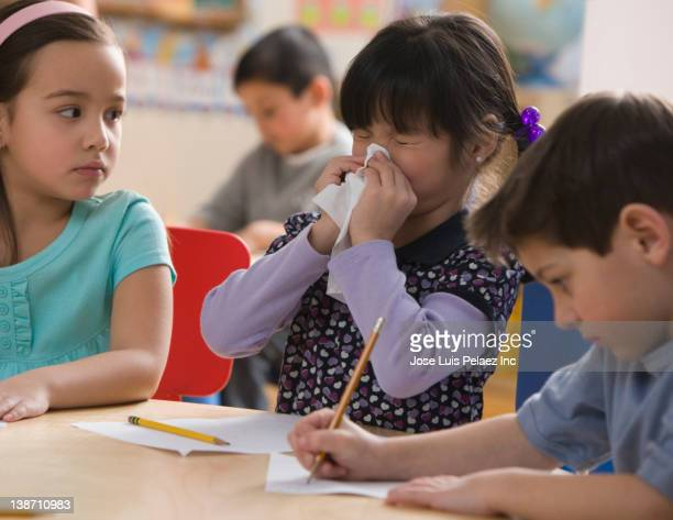 mixed race girl blowing nose in classroom - infectious disease stock pictures, royalty-free photos & images