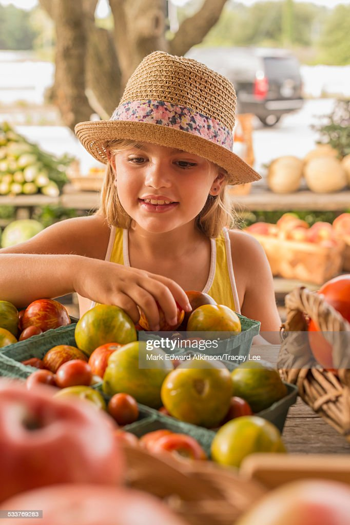 Mixed race girl browsing produce at farmers market : Foto stock