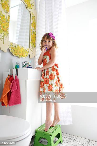 Mixed race girl brushing her teeth