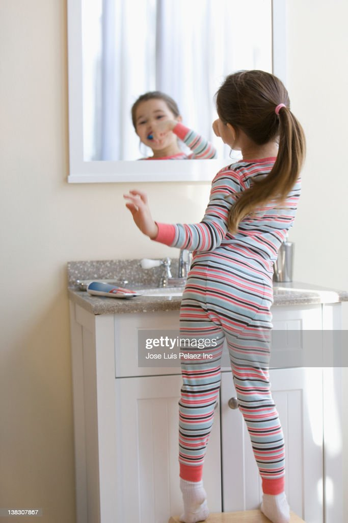 Mixed race girl brushing teeth : Stockfoto