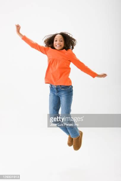 Mixed race girl cheering and jumping