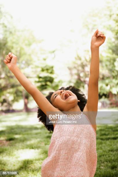 Mixed race girl cheering with arms raised