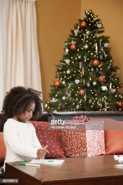 Mixed race girl coloring in living room with Christmas tree