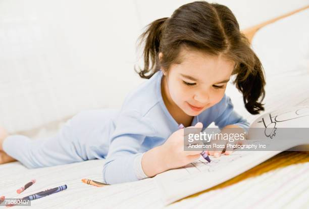 Mixed Race girl coloring on bed