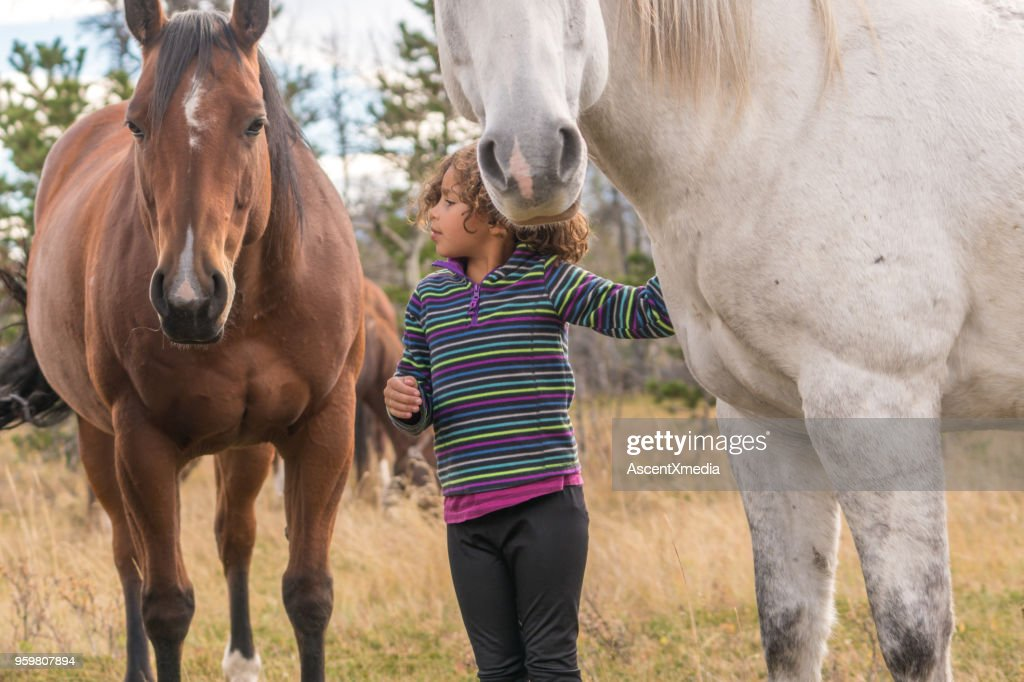 Gemischte Rassen Mädchen verbindet mit Pferden unter Bergen : Stock-Foto