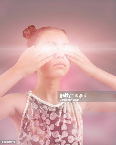 Mixed race girl covering glowing eyes