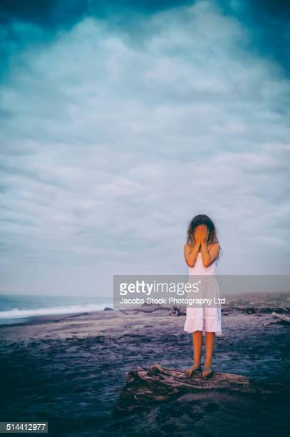 Mixed race girl covering her face on beach