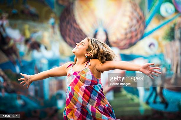 Mixed race girl dancing near urban rural