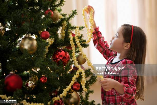 mixed race girl decorating christmas tree - christmas garland stock pictures, royalty-free photos & images