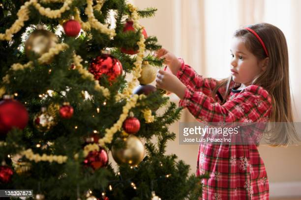 mixed race girl decorating christmas tree - garland decoration stock pictures, royalty-free photos & images