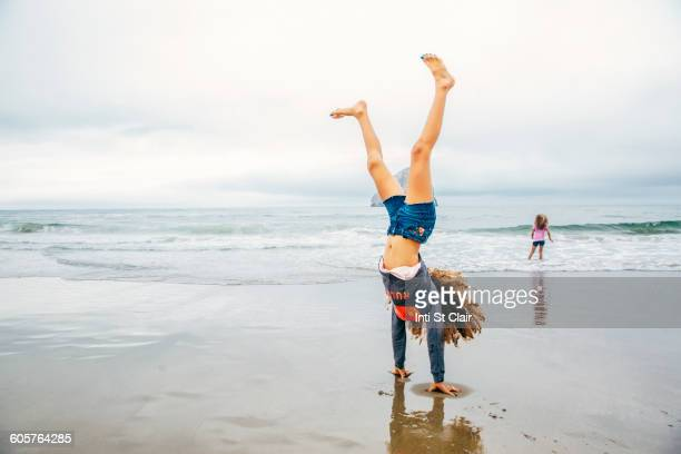 Mixed race girl doing handstand on beach