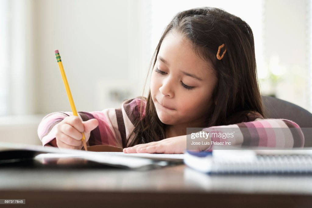 Mixed race girl doing homework : Stock-Foto