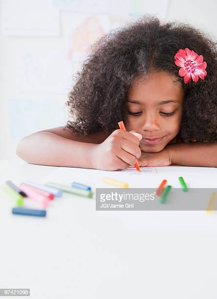 Mixed race girl drawing with crayons