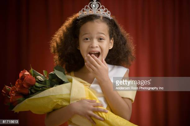 Mixed Race girl dressed as beauty queen