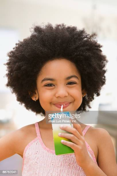 mixed race girl drinking juice box - juice carton stock photos and pictures