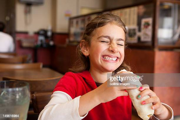 Mixed race girl eating burrito in restaurant