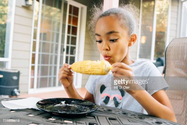 mixed race girl eating corn on the cob outdoors - hot indian girls stock photos and pictures