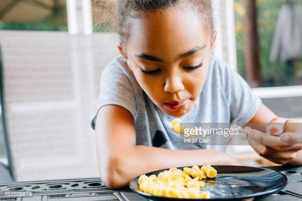 mixed race girl eating food with fork - hot indian girls stock photos and pictures