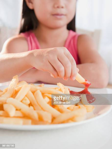 Mixed race girl eating French fries and ketchup
