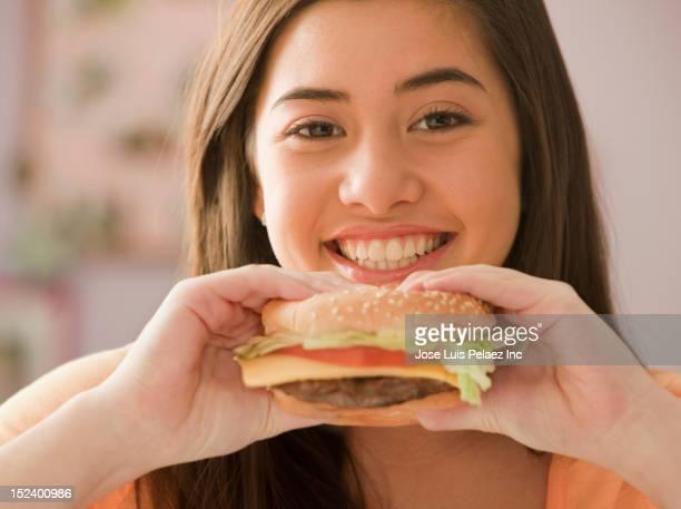 Mixed race girl eating hamburger