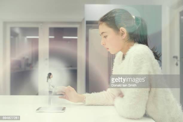 Mixed race girl examining hologram projection